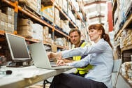 warehouse staff looking at inventory on laptop